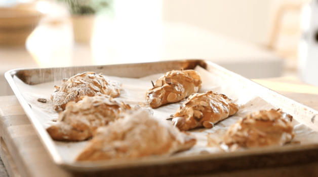 easy almond croissants recipe fresh out of the oven on a parchment lined baking sheet