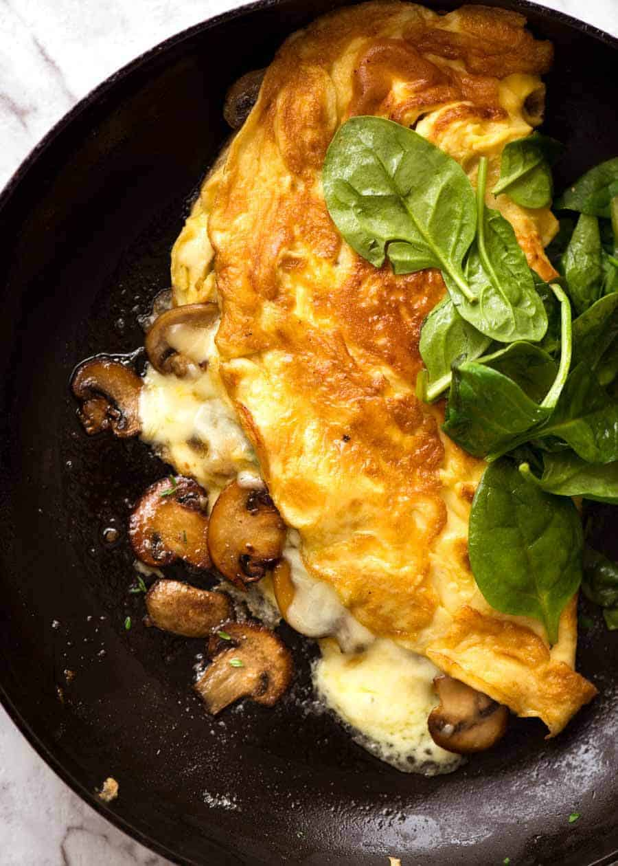 Overhead photo of Cheesy Omelette with Garlic Butter Mushrooms in a skillet.